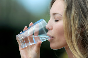 Closeup of blond woman drinking water from glass